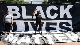 Eine Frau posiert auf einem großen Black Lives Matter Banner während der Proteste in Washington D.C. (© picture alliance/ZUMAPRESS.com) © picture alliance/ZUMAPRESS.com Foto: Michael Brochstein