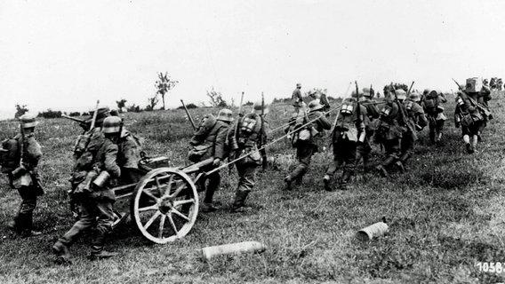 Deutsche Soldaten ziehen im Ersten Weltkrieg ein Geschütz über eine Wiese. © imago/United Archives