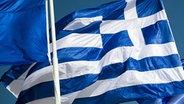 Neben einer Griechenlandfahne weht die Flagge der EU. © dpa bildfunk Fotograf: Michael Kappeler