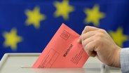 Ein Mann steckt einen Wahlbrief zur Europawahl in eine Wahlurne. © dpa Foto: Patrick Pleul