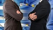 Zwei Personen im Anzug stehen mit sich mit eingeschränkten Armen vor einer Griechenland-EU Flagge gegenüber. (Bildmontage) © fotolia.com Fotograf: BillionPhotos.com, TR
