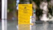 Ein klassischer analoger Impfpass steht neben einer Impfdosis und einer Spritze auf einem Tisch. Bild: picture alliance / Geisler-Fotopress | Dwi Anoraganingrum/Geisler-Fotop © picture alliance / Geisler-Fotopress | Dwi Anoraganingrum/Geisler-Fotop Foto: Geisler-Fotopress