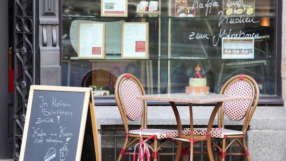 """Sachsen, Leipzig: Eine Tafel mit Aufschrift """"In kleinen Schritten zurück! Kaffee und Kuchen zum Mitnehmen"""" steht neben abgesperrten Sitzplätzen vor einem Café. (© picture alliance/Jan Woitas/dpa-Zentralbild/dpa) © picture alliance/Jan Woitas/dpa-Zentralbild/dpa Foto: Jan Woitas"""