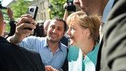 Bundeskanzlerin Angela Merkel (CDU) lässt sich am 10.09.2015 nach dem Besuch einer Erstaufnahmeeinrichtung für Asylbewerber in Berlin-Spandau für ein Selfie zusammen mit einem Flüchtling fotografieren. ©  picture alliance / dpa Fotograf:  Bernd Von Jutrczenka