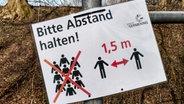 Ein Schild weist auf den Mindestabstand hin, den Menschen einhalten sollen. © picture alliance/ZUMA Press Foto: Sachelle Babbar