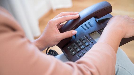 Eine Frau greift nach einem Telefonhörer. © picture alliance / dpa Themendienst Foto: Christian Klose