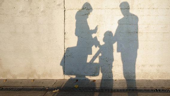Die Schatten einer Frau, eines Kindes und eines Mann vor einer Mauer. © photocase.de Foto: krockenmitte
