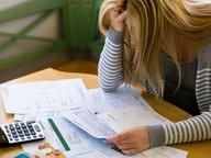 Eine Frau beugt sich verzweifelt über eine Rechnung © Fotolia.com Fotograf: Gina Sanders
