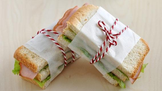 Zwei mit einem Faden zusammengebundene Sandwiches. © fotolia Foto: A Lein