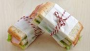 Zwei mit einem Faden zusammengebundene Sandwiches. © fotolia Fotograf: A Lein