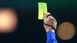Ein Schiedsrichter hält eine gelbe Karte hoch ©  picture-alliance / ASA Fotograf: WEREK