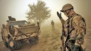 Ein Soldat winkt ein gepanzertes Fahrzeug zu sich heran. © picture alliance / JOKER Foto: Timo Vog