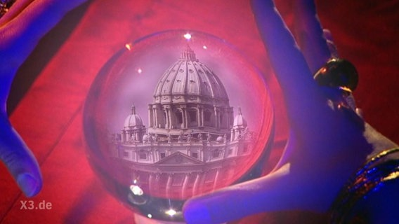 Eine Glaskugel zeigt die Kuppel des Petersdom.