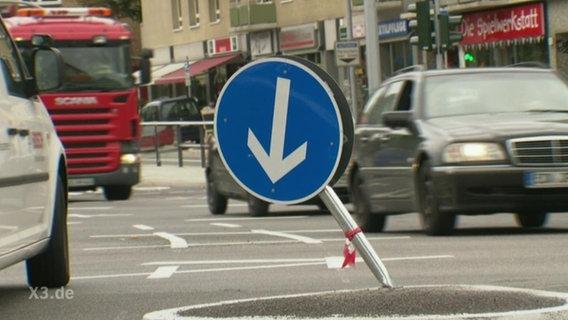 Ein abgeknicktes Gebotsschild auf einer Verkehrskreuzung.