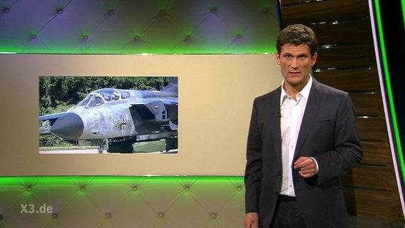 Christian Ehring vor einem Bild eines Kampfjets der Bundeswehr.