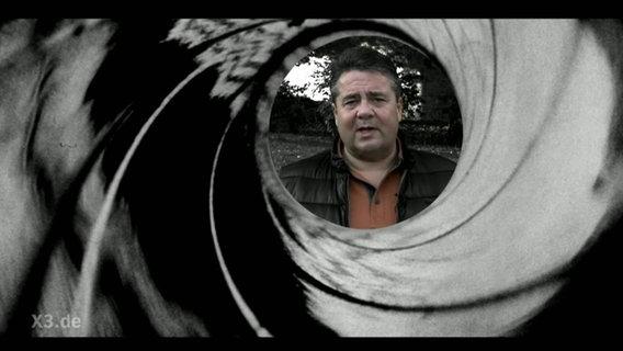 Sigmar Gabriel durch den Lauf eines Gewehrs fotografiert.