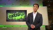 """Christian Ehring vor dem Logo der Sendung """"Extra 3""""."""