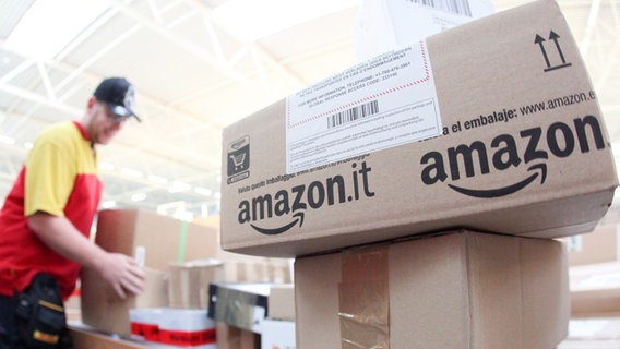 Ein Paketzusteller sortiert Pakete von Amazon.  Foto: Bodo Marks