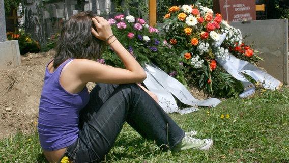 Eine junge Frau trauert an einem Grab © picture alliance