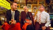 Jan Böhmermann (links) und Götz Alsmann sitzen mit Ina Müller bei Inas Nacht auf dem Tresen. © NDR/Morris Mac Matzen