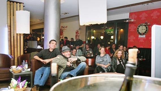 Mitarbeiter und Künstler sehen sich im gegenüberliegenden Cafe gemeinsam die Aufzeichnung an. © NDR Foto: Christian Spielmann
