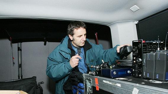 Ein Techniker beim Einpacken von Equipment © NDR Foto: Christian Spielmann