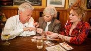 Ina Müller (Mitte) und Palina Rojinski kleben Max Moor falsche Fingernägel auf. © NDR/Morris Mac Matzen