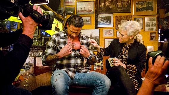 Tim Wiese sitzt mit Ina Müller bei Inas Nacht am Tresen und entblößt seine tätowierte Brust. © NDR/Morris Mac Matzen
