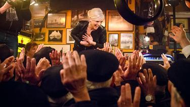 Ina Müller steht bei Inas Nacht auf dem Tresen des Schellfischposten, Hände strecken sich ihr entgegen. © NDR/Morris Mac Matzen