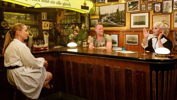 Lisa Maria Potthoff, Jenke von Wilmsdorff und Ina Müller sitzen um einen Tresen und unterhalten sich. © NDR/Morris Mac Matzen