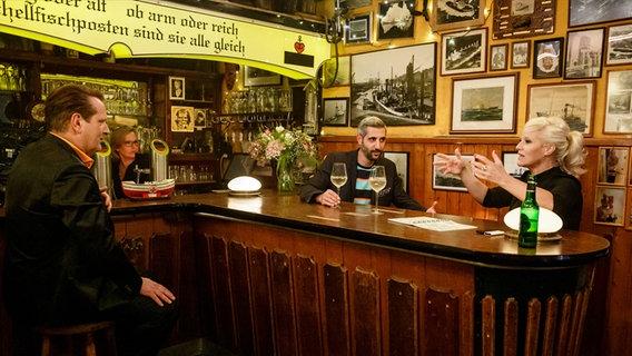 Ralf Dümmel, Michel Abdollahi und Ina Müller sitzen um einen Tresen und unterhalten sich. © NDR/Morris Mac Matzen