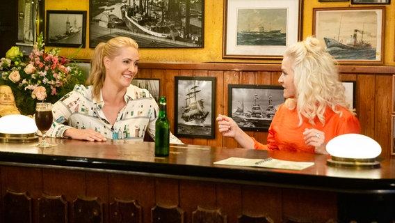 Judith Rakers und Ina Müller sitzen nebeneinander an einem Tresen. © NDR/Morris Mac Matzen Foto: Morris Mac Matzen