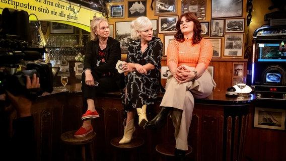 """Elke Heidenreich, Ina Müller und Sophie Passmann sitzen auf dem Tresen des """"Schellfischpostens"""". © NDR/ Morris Mac Matzen Foto: Morris Mac Matzen"""