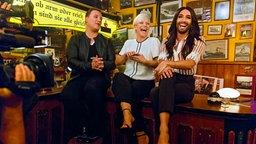 Conchita Wurst sitzt bei Inas Nacht mit Ina und Guido Maria Kretschmer auf einem Tisch und beantwortet lachend Bierdeckelfragen. © NDR/Morris Mac Matzen