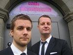 Tobias Schlegl und York Pijahn vor der Schuldenuhr in Berlin.
