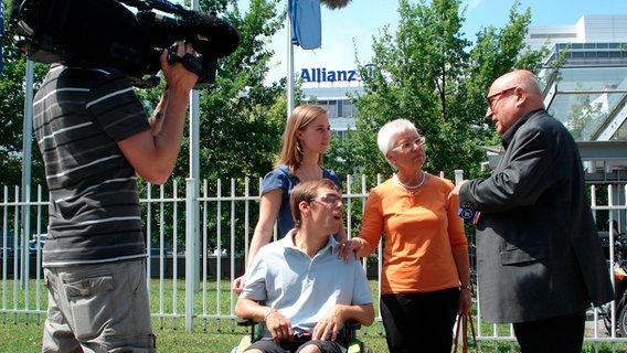 Christoph Lütgert mit Versicherungsopfern vor einem Gebäude der Allianz. © NDR