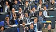 Abgeordnete der AfD-Fraktion sitzen im Bundestag auf ihren Plätzen und heben bei einer Abstimung ihre Hände. © dpa-Bildfunk Foto: Bernd von Jutrczenka