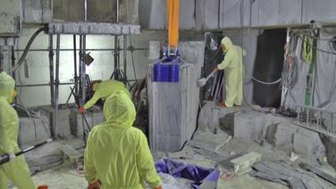 Arbeiter bauen ein AKW zurück.