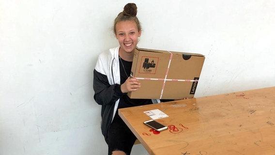 Die Hamburger Schülerin Jana hält einen im Paket befindlichen Laptop in den Händen. © NDR/ARD