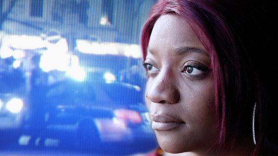 Elisabeth M. vor einem Hintergrund aus Polizeifahrzeugen mit Blaulicht. © NDR / ARD