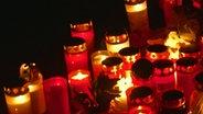 Kerzen stehen am Ort des Brandanschlages auf Delali A.