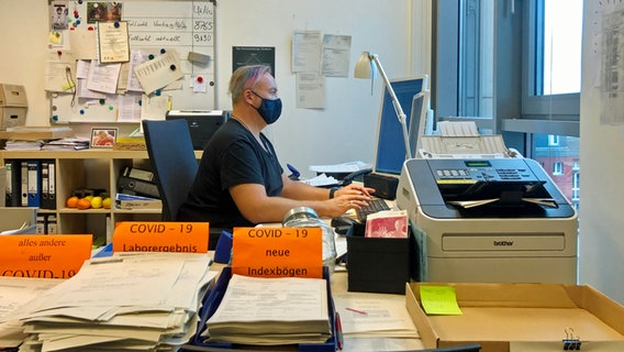 Eine Person sitzt mit Mundschutz vor einem Computer, im Vordergrund Ablagekästen mit Corona-Testergebnissen © NDR/ARD Foto: Screenshot