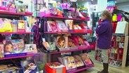 Ein Mädchen steht vor einem Regal mit Kinderspielzeug