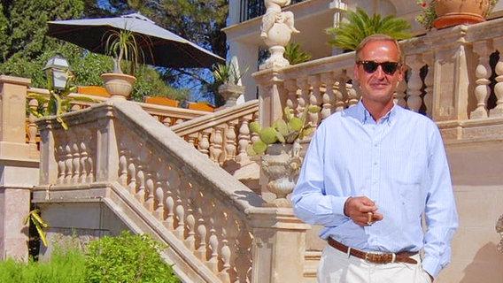 Florian Homm steht vor einer Treppe.