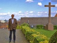 Florian Homm steht neben einem Kreuz.