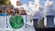 Bildcollage aus einer Demonstration von Fridasy for Future und rauchenden Kraftwerksschornsteinen
