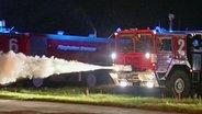 Ein Feuerwehrauto sprüht Löschschaum.