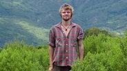 """Finn Bogumil aus Hamburg steht vor bewaldeten Bergen. Er glaubte an die sogenannte """"Lichtnahrung"""". © NDR Foto: Screenshot"""