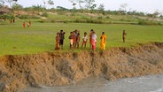 Kinder stehen an der Abbruchkante eines Flusses in Bangladesch.  Foto: Maike Rudolph