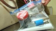 Flüssigkeiten werden in einen durchsichtigen, mit Reißverschluß versehenen Plastikbeutel verpackt. © dpa - Report Foto: Holger Hollemann